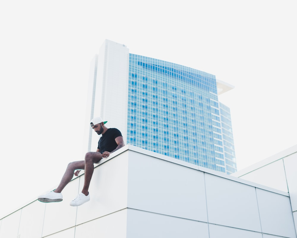 man sitting at the roof of the building