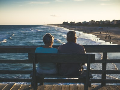 man and woman sitting on bench in front of beach emerald isle zoom background