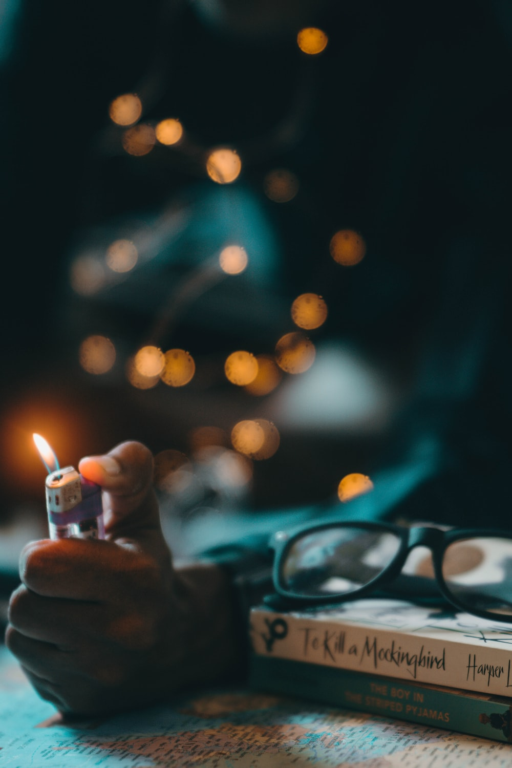 selective focus photography of person lighting up lighter with bokeh background