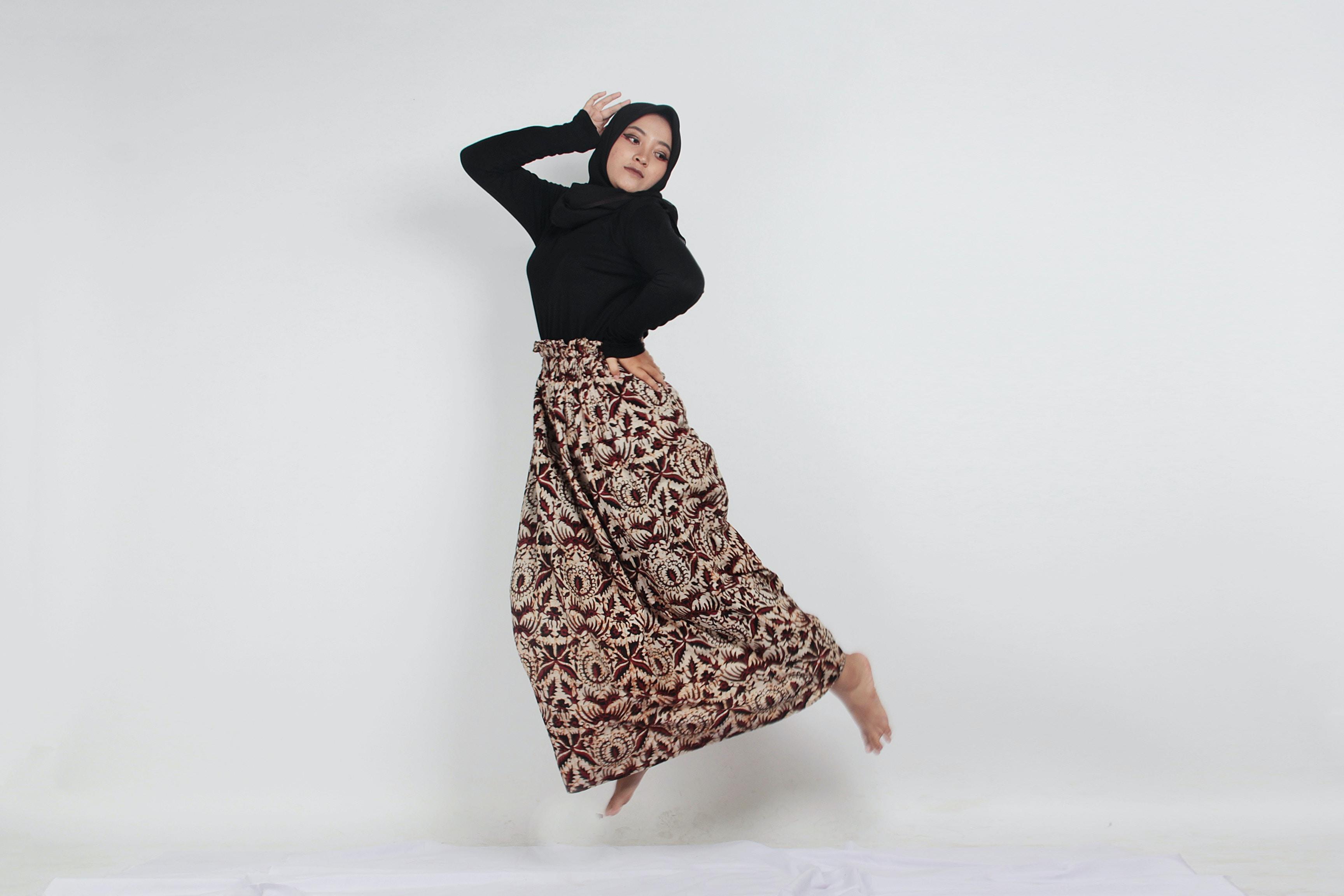 woman wearing black hijab doing jump shot