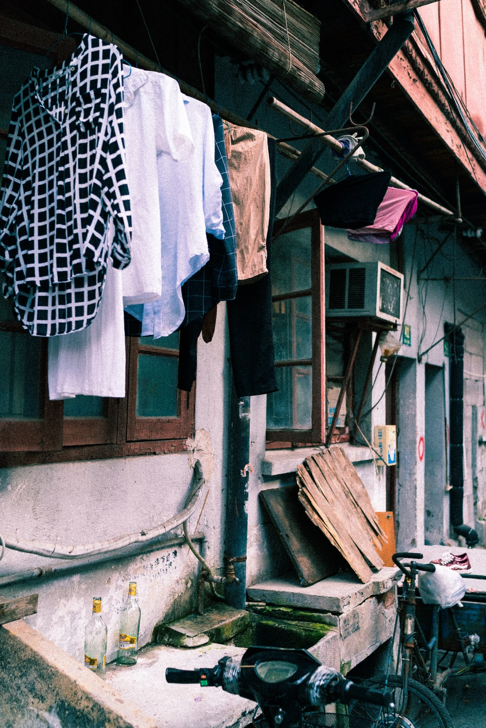 assorted clothes hanged on clothesline outside window