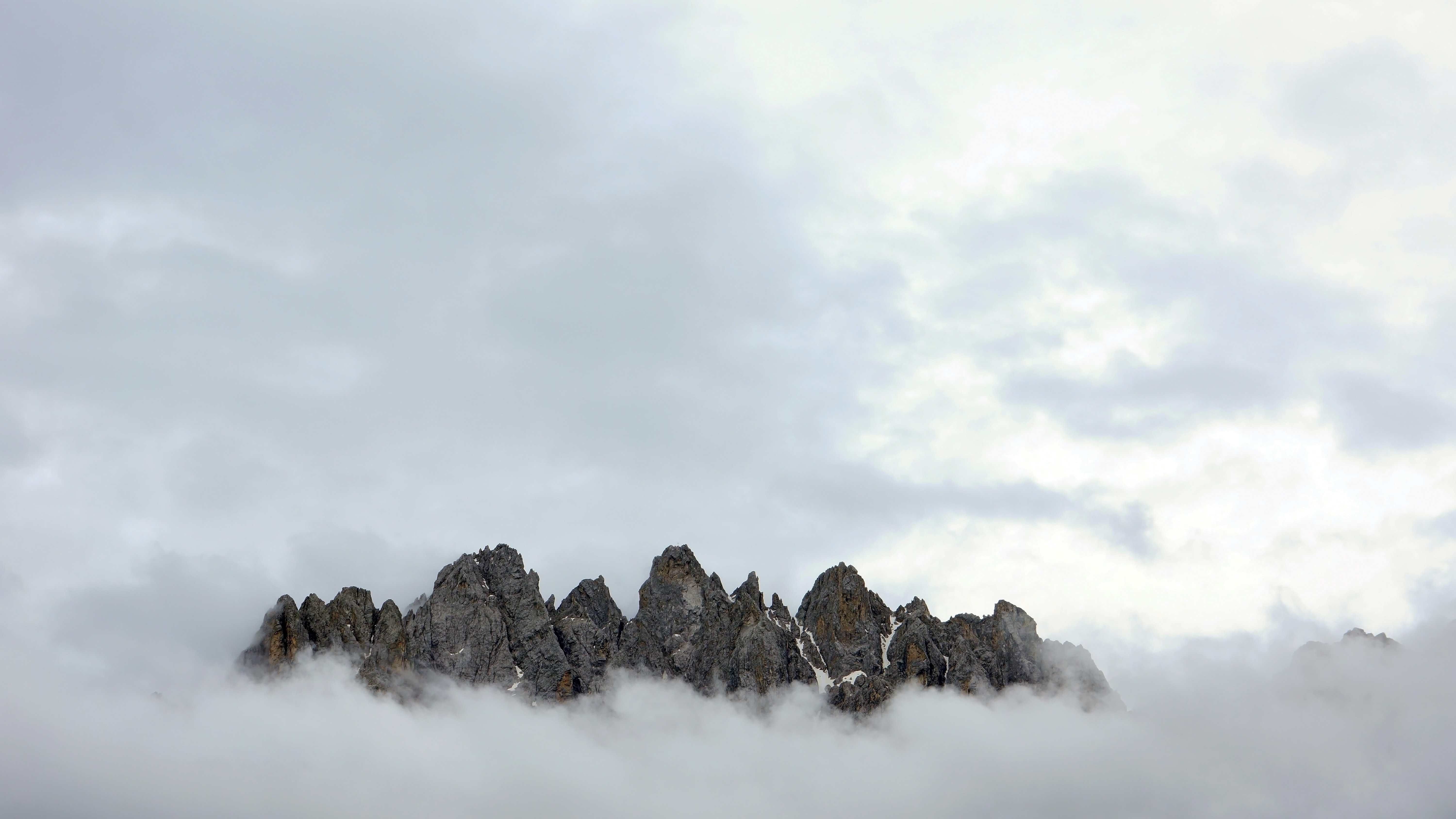 low-angle photo of mountain covered with fog during daytime