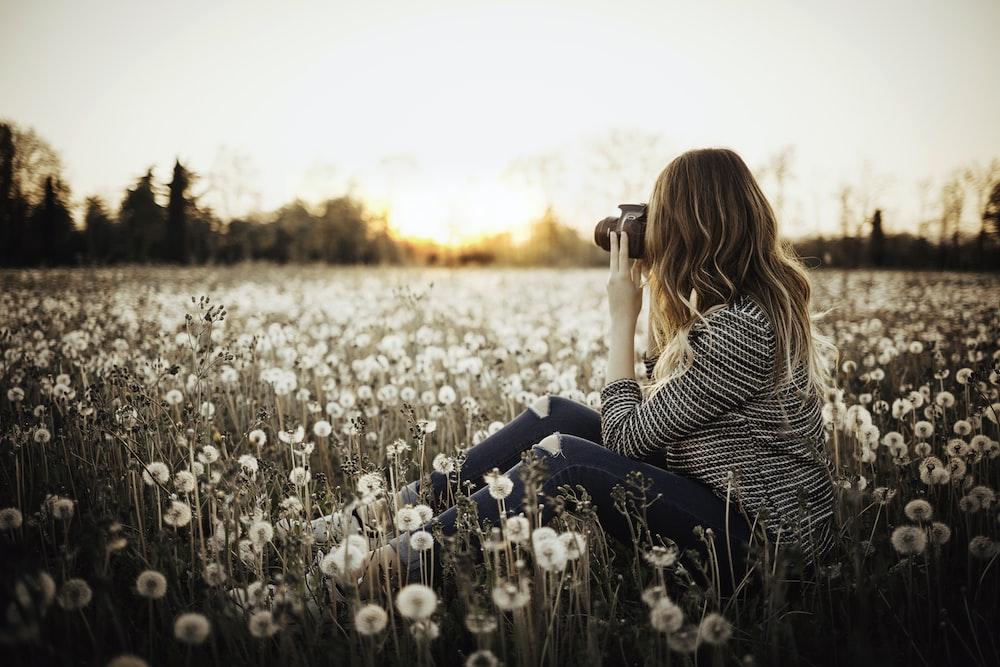 woman sitting on flower field taking photo of trees