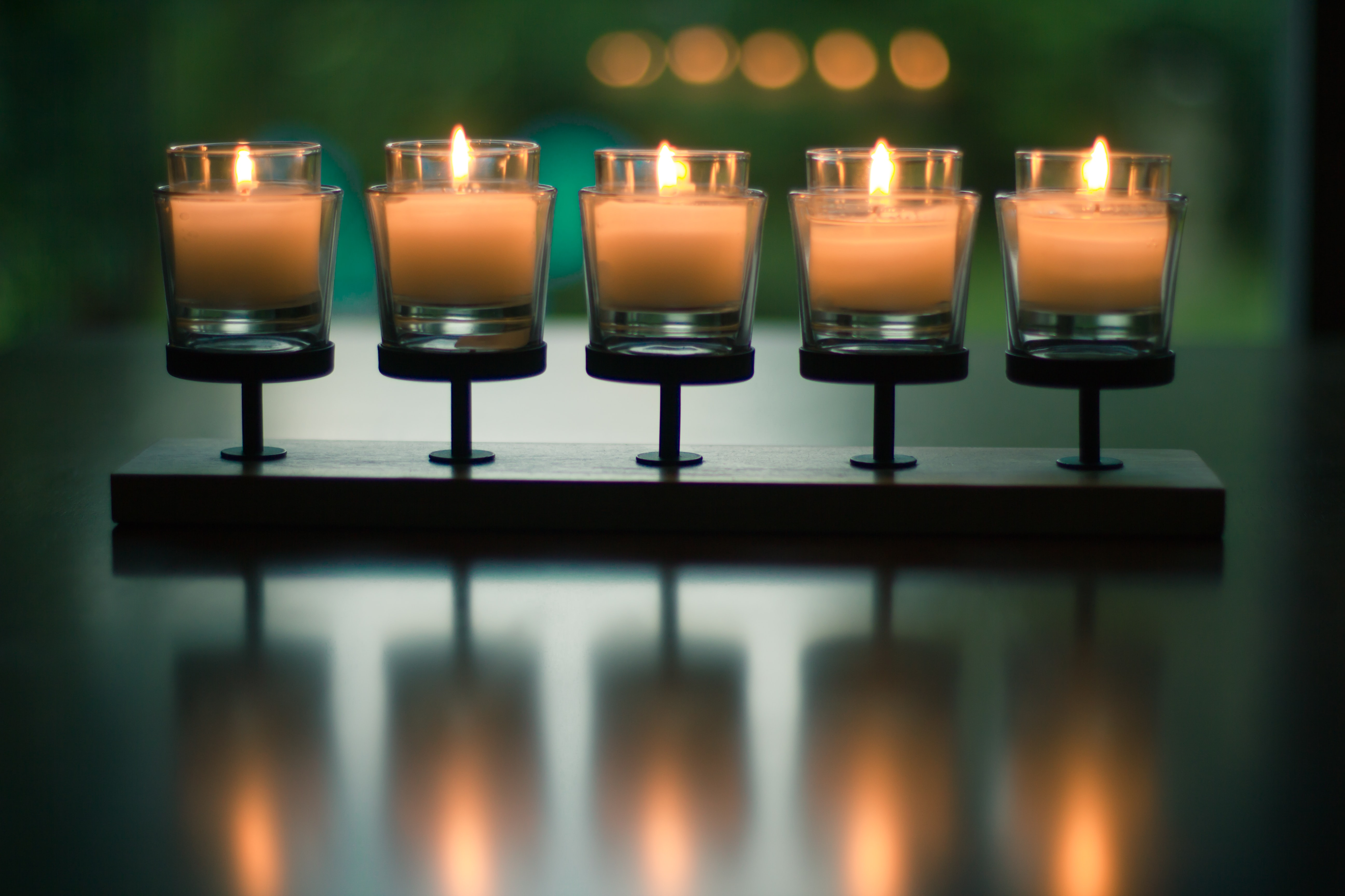 bokeh photography of five lighted votive candles