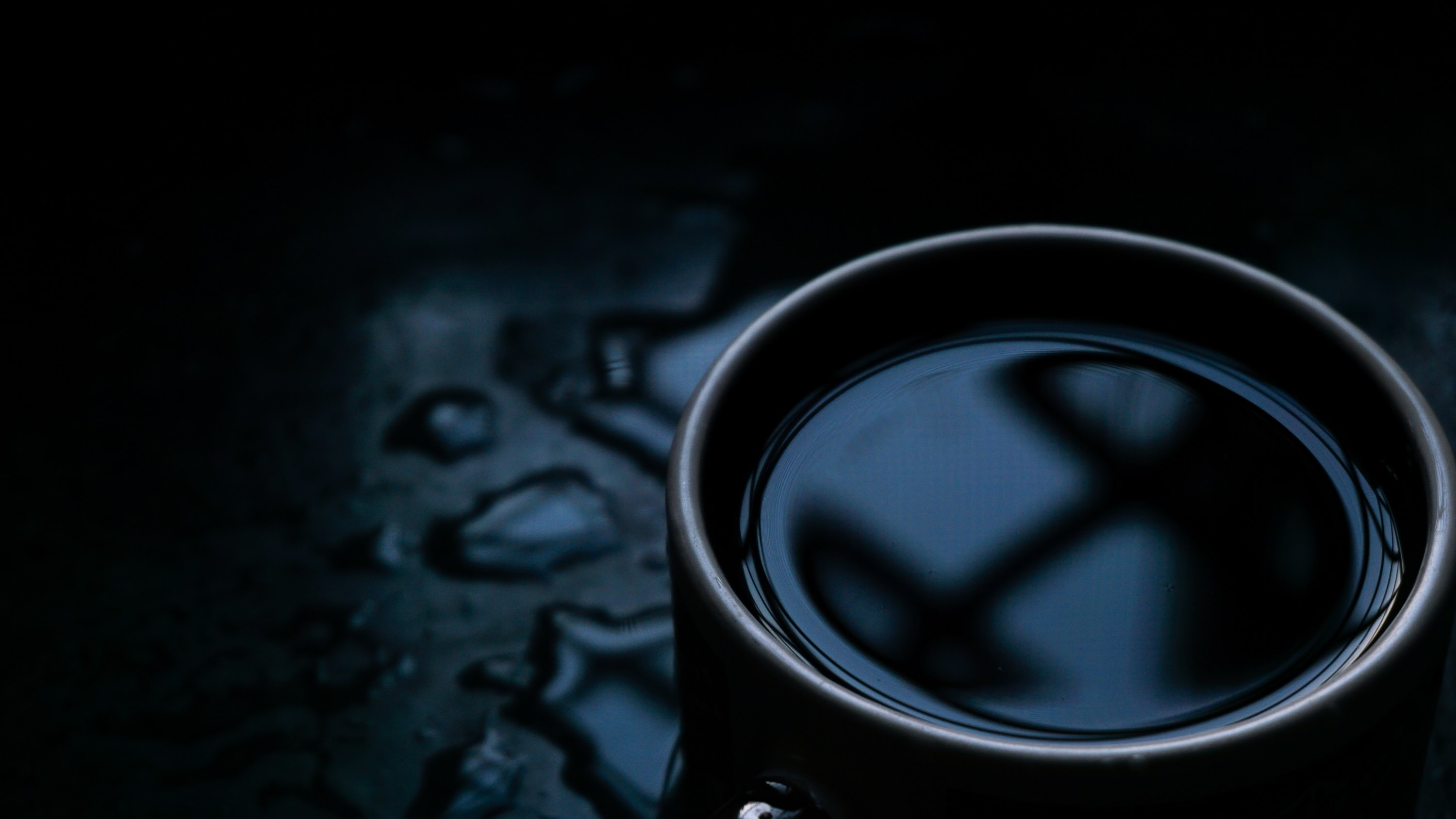 black ceramic mug on wooden surface