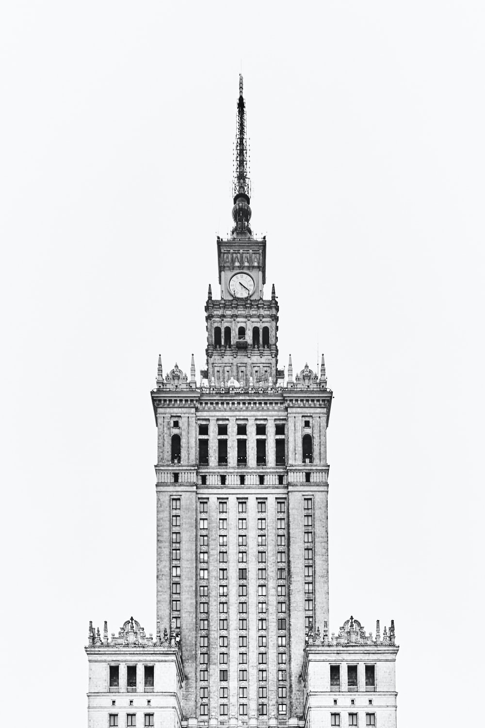 grayscale photo of Gothic concrete tower clock