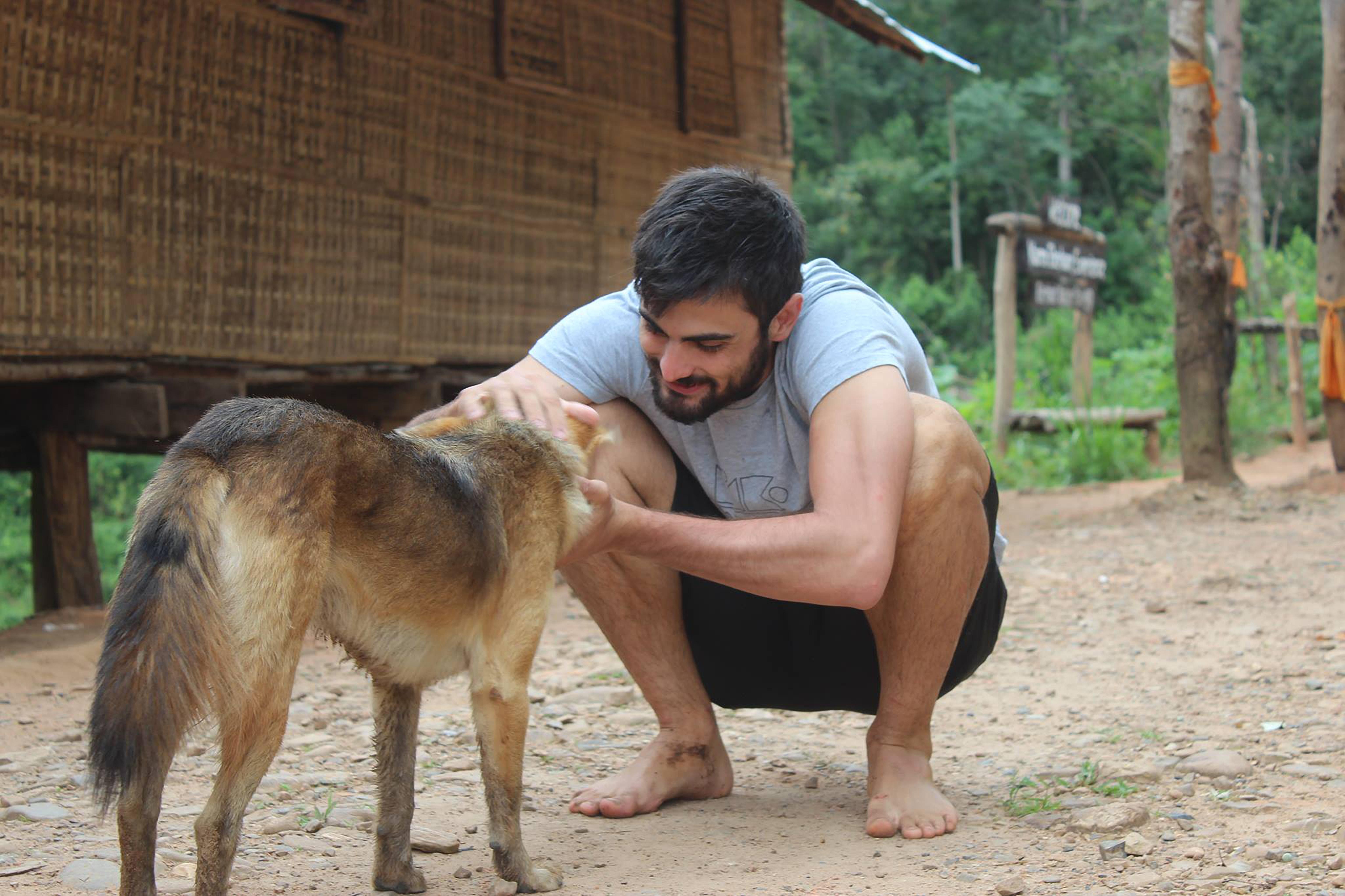 man petting brown dog