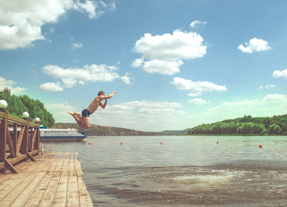 man diving on lake