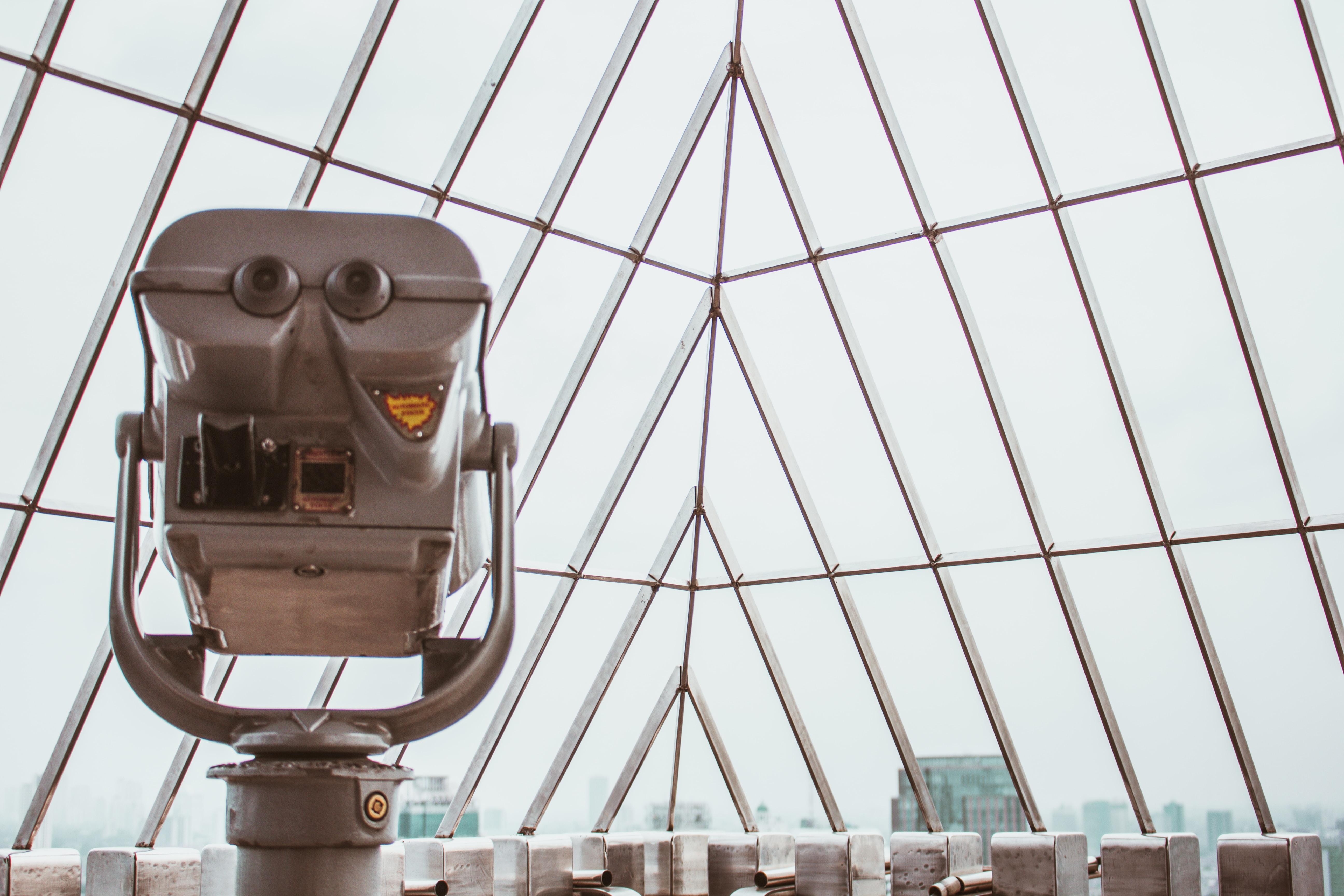 gray binocular viewer near glass curtain wall