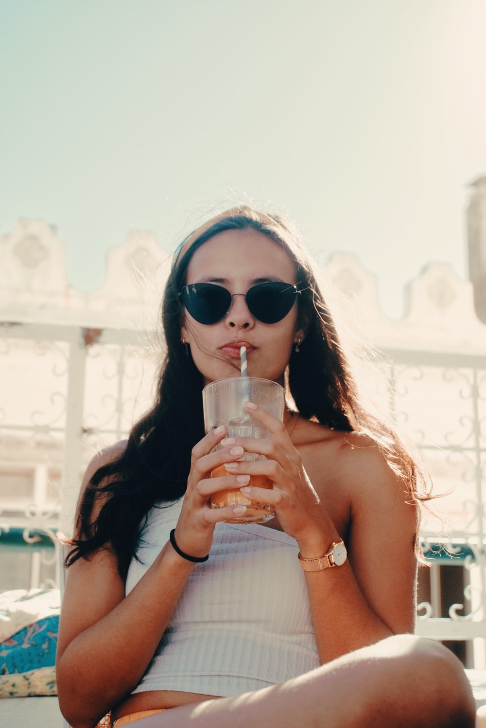 woman sipping straw in glass