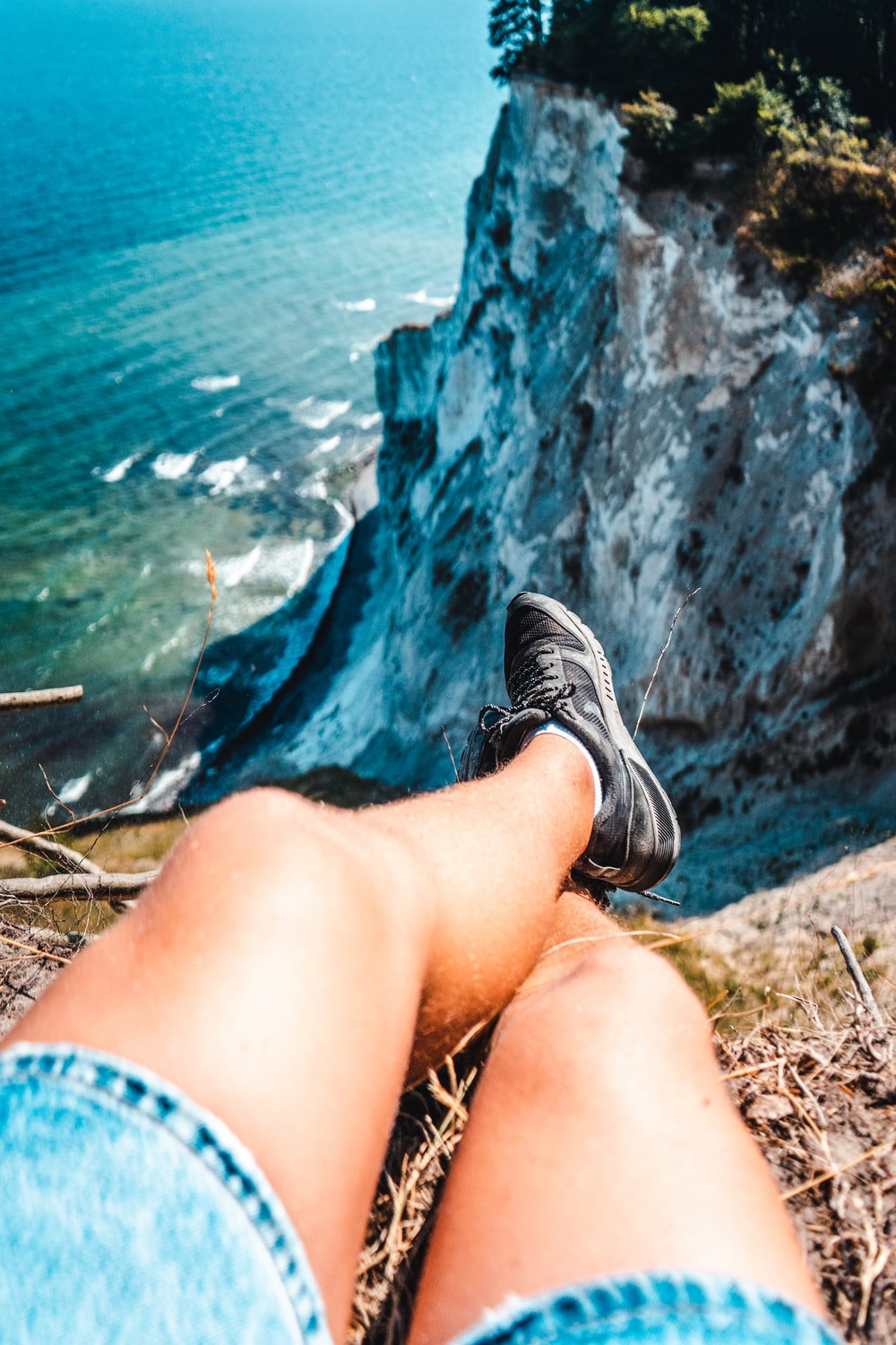 person wearing black-and-gray shoes and blue denim shorts sitting on mountain cliff