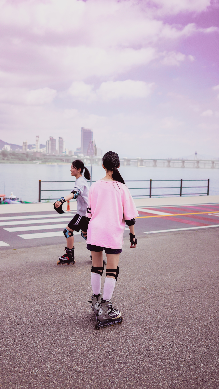 two girls playing inline skates near body of water during daytime