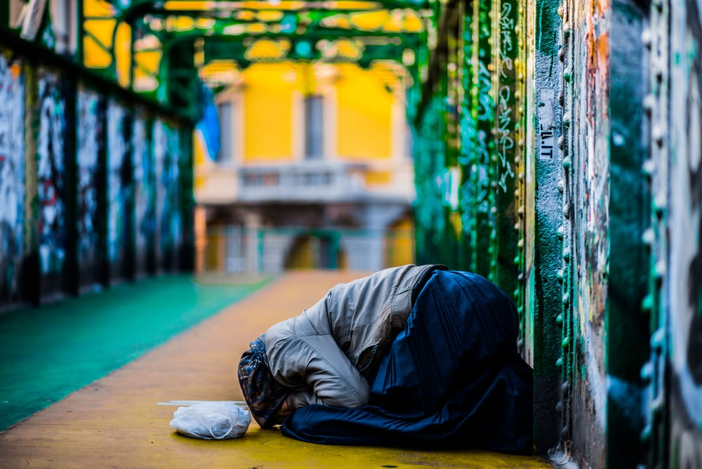 selective focus photography praying woman on pavement