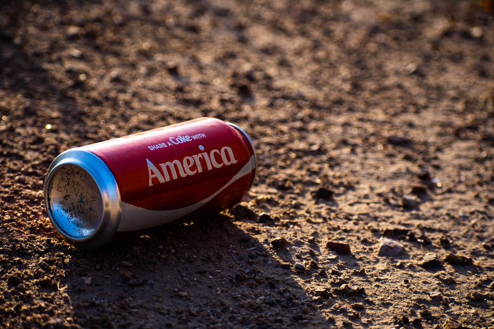 Coca-Cola America tin can on brown soil