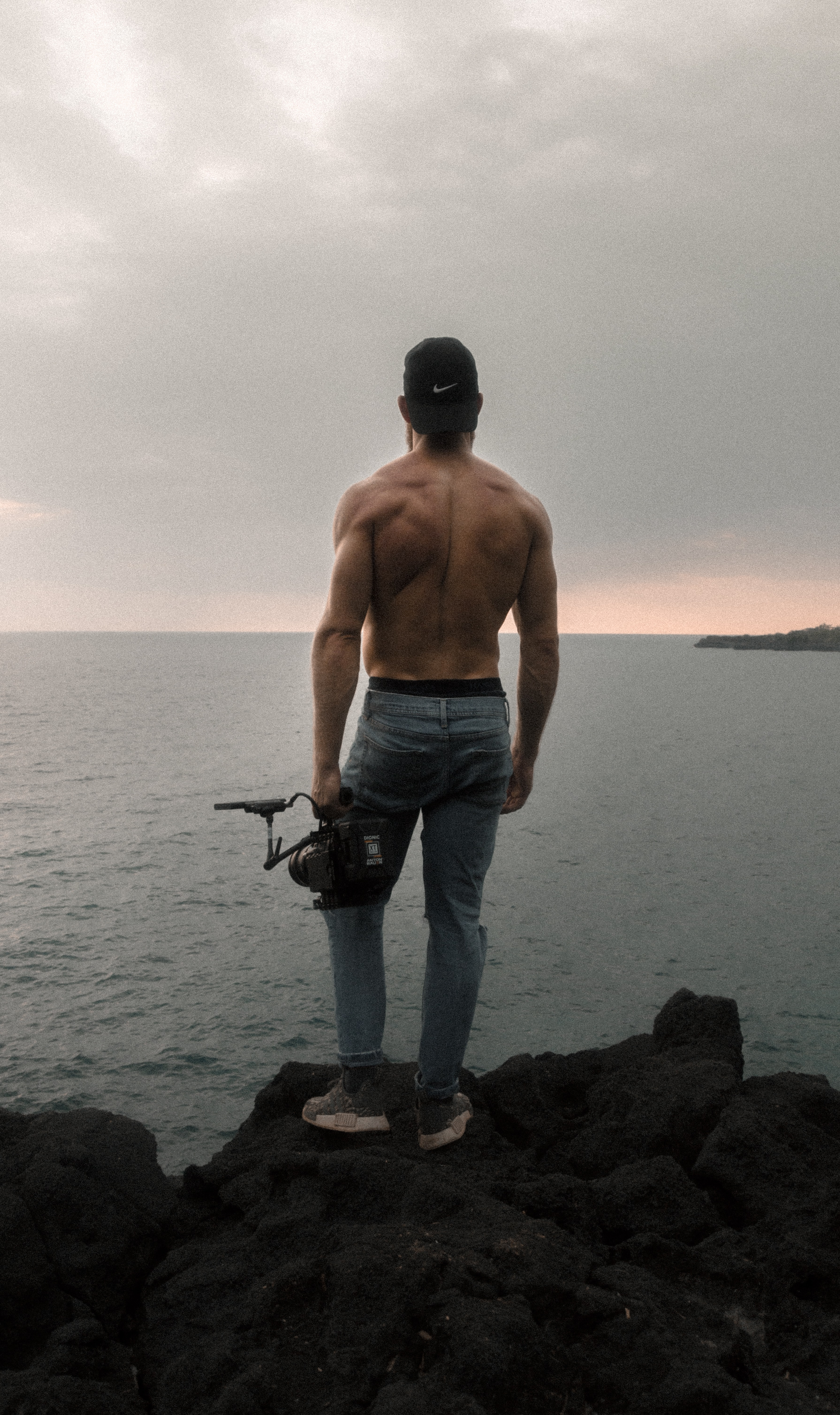back view of topless man standing on cliff while holding camera