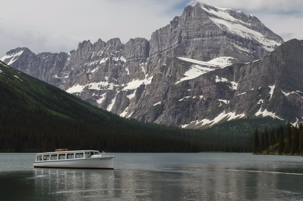 white cruise ship on body of water near rocky mountain