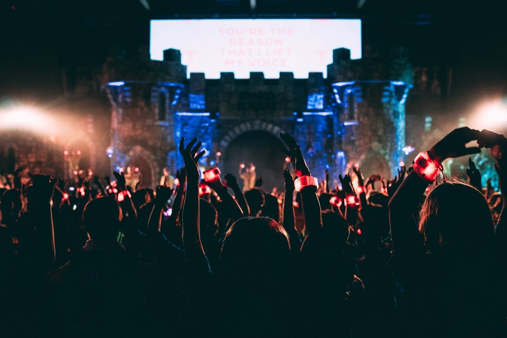 crowded people wearing LED bracelet raising hands in front of stage