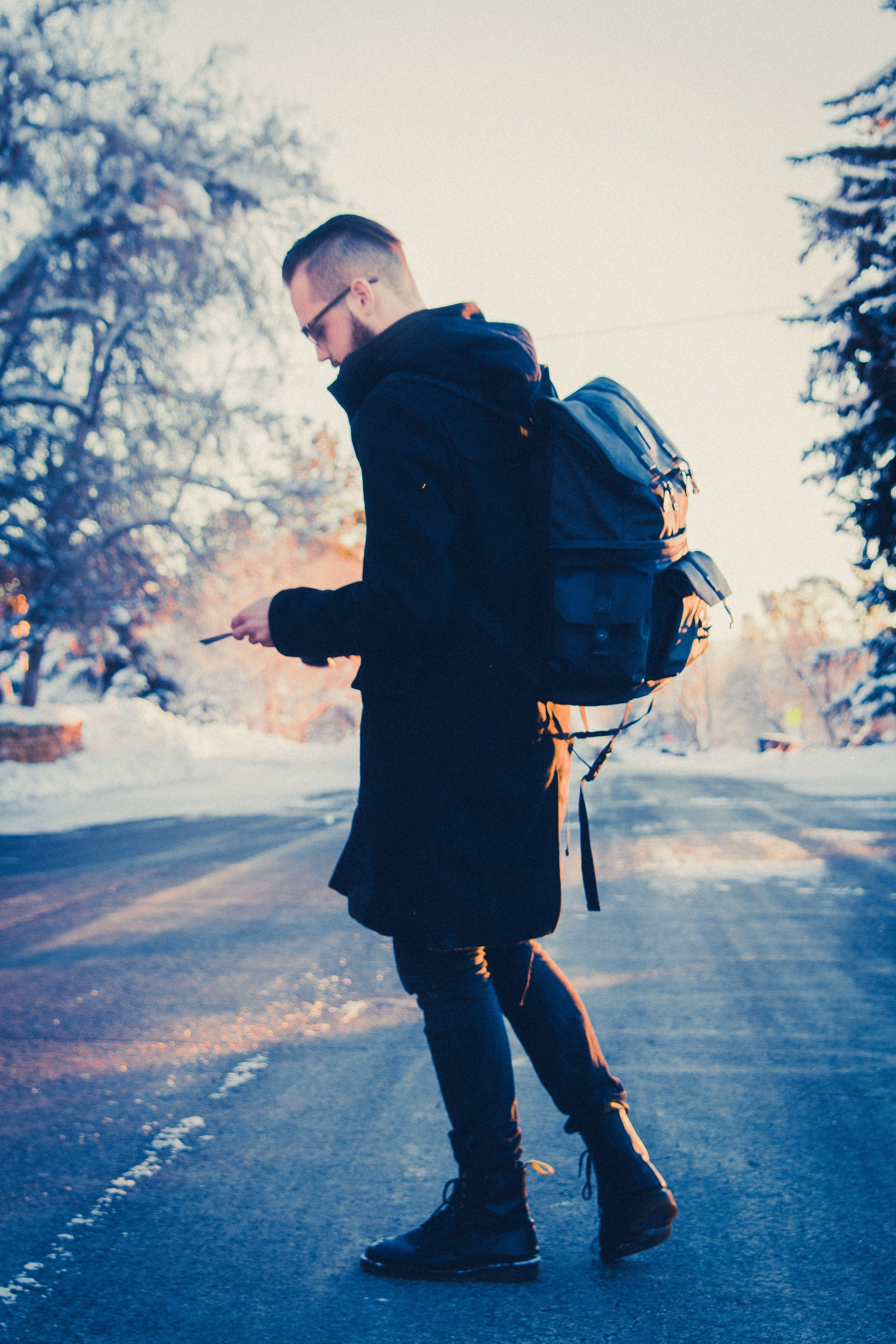 selective focus photography of man in black coat carrying gray backpack