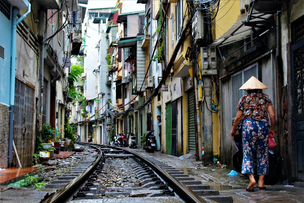 person walking on railway side between buildings at daytime