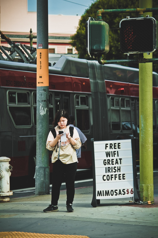 woman using phone near traffic light