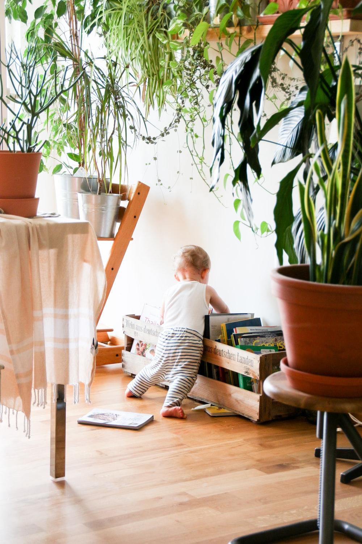 toddler wearing white tank top near white wall