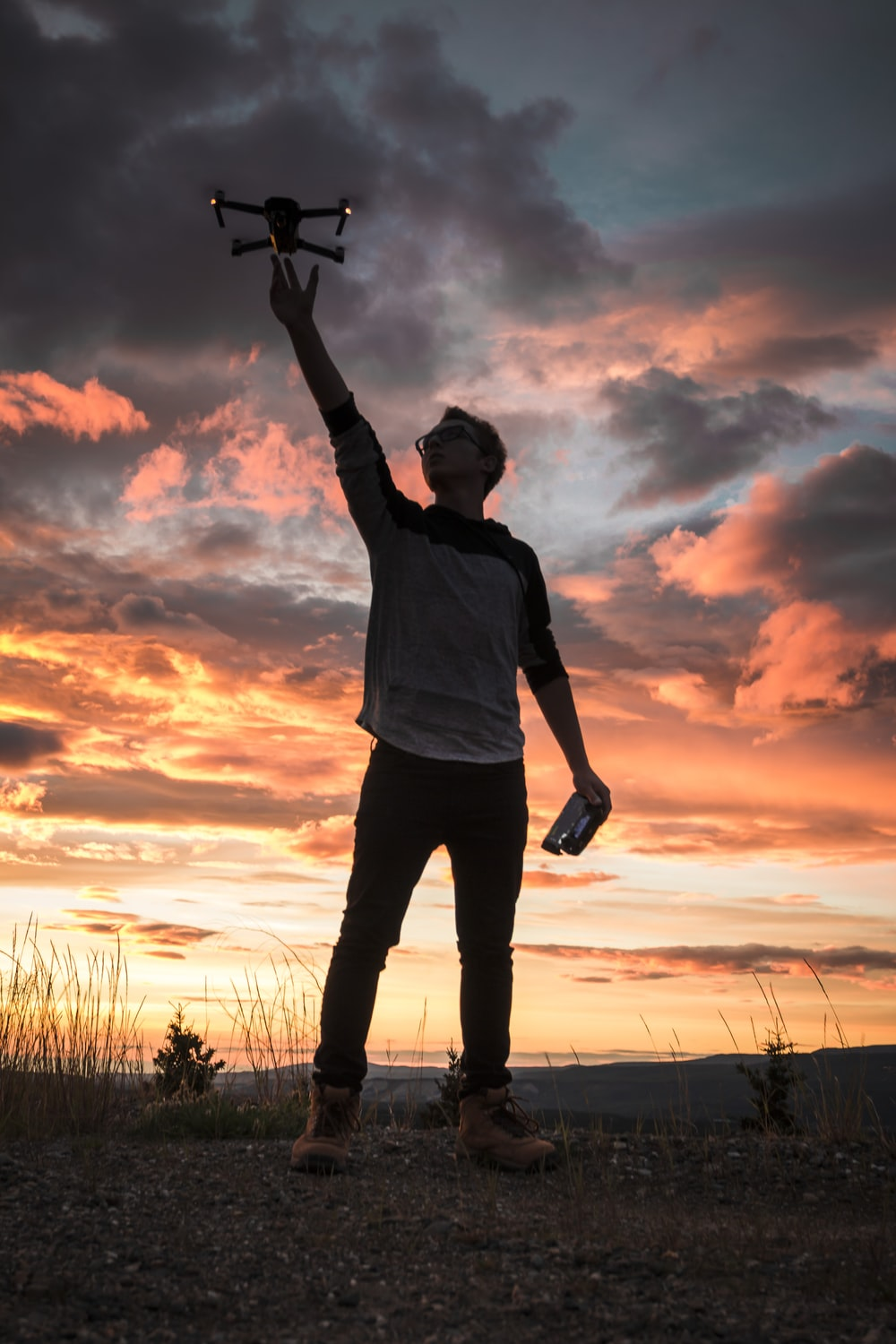 silhouette photo of man holding up drone