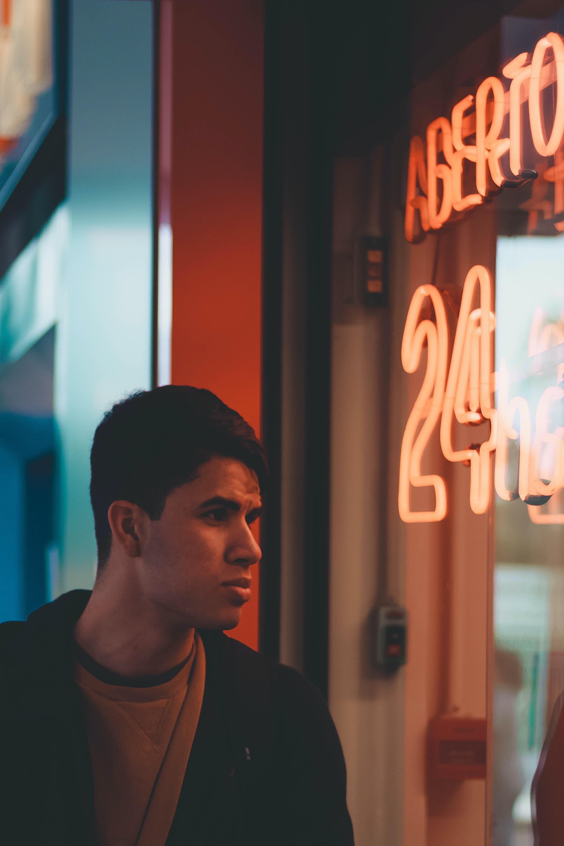 man standing beside glass wall watching outside