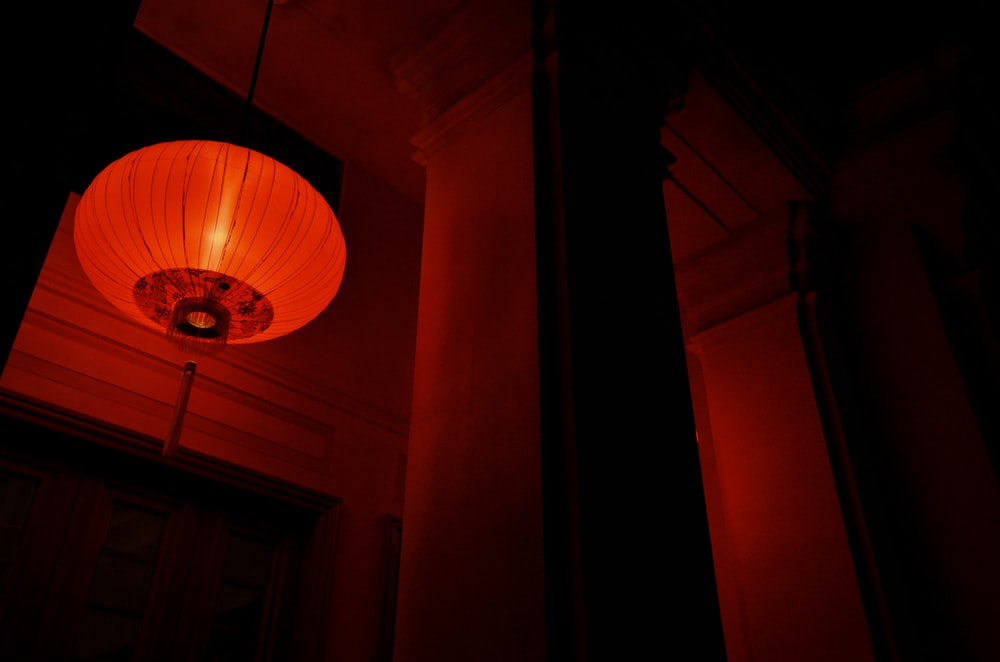 low angle photo of lighted red paper lantern