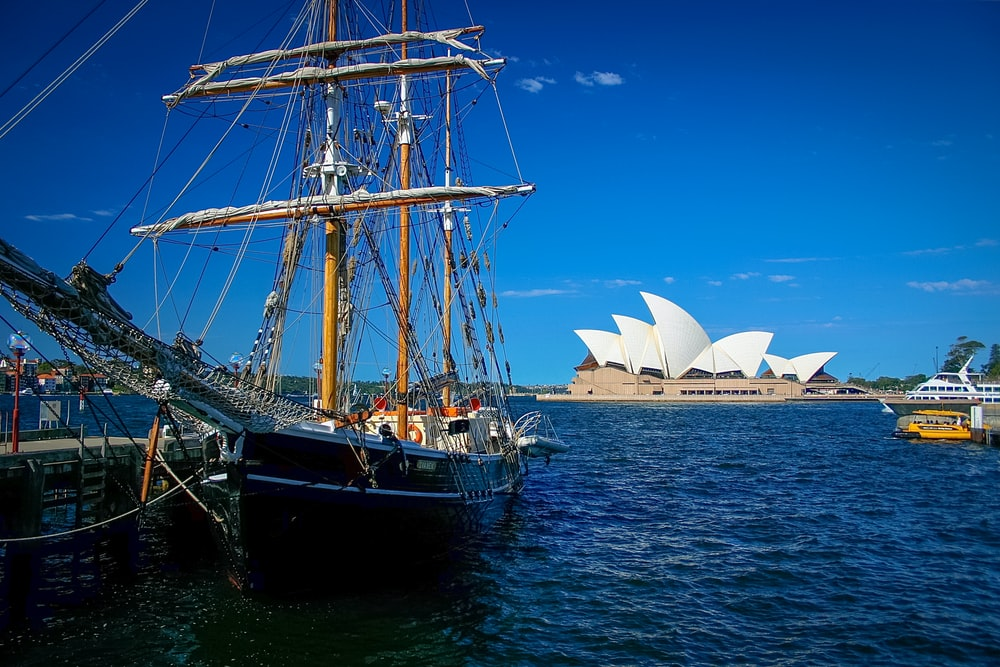 brown and black sailboat near Sydney Opera House