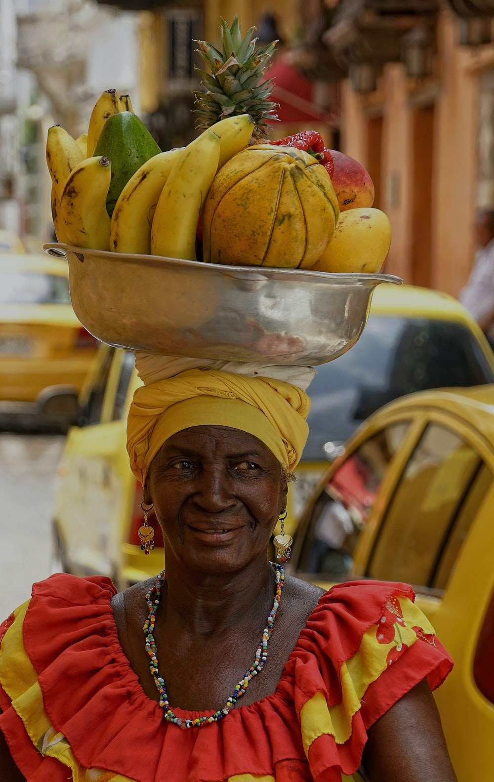 woman carrying fruits in bowl