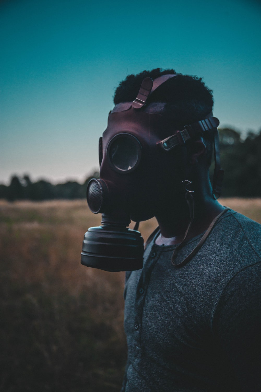 man wearing brown gas mask standing on brown field