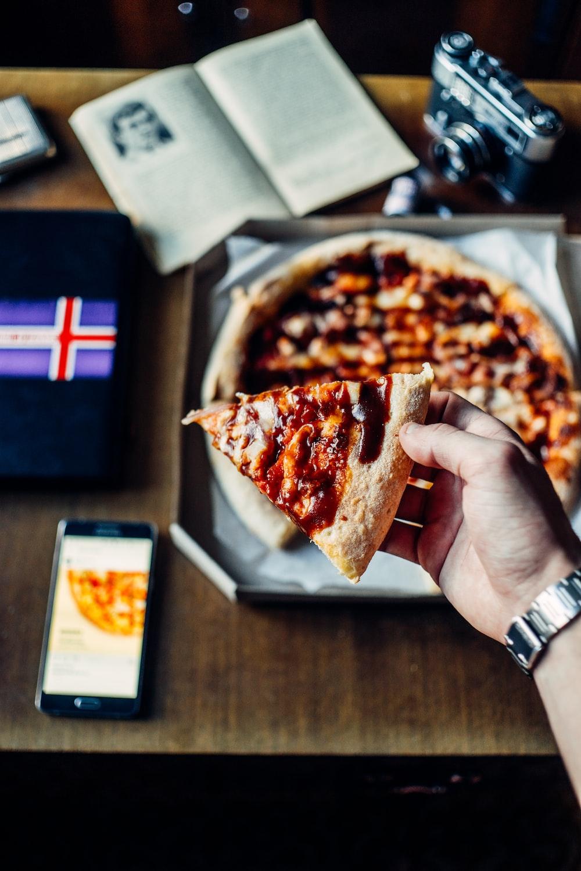 person holding pizza slice