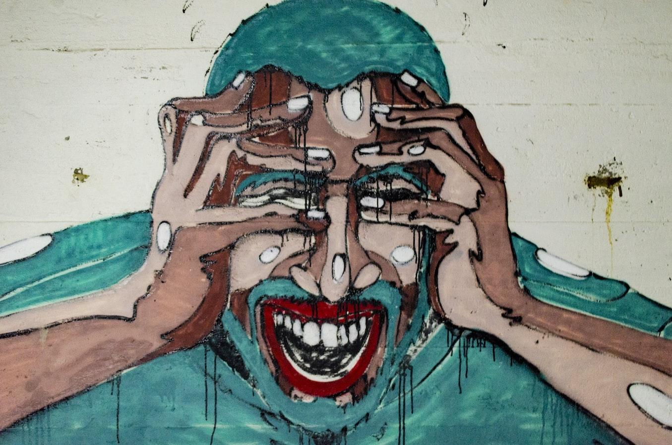 Grafitti muže v bolesti s rukama na obličeji.