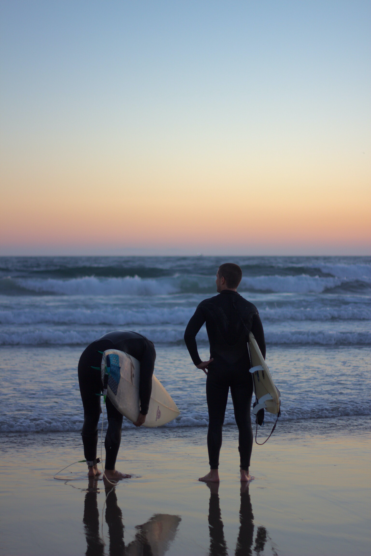 two person in black wetsuit holding surfboards standing on beach