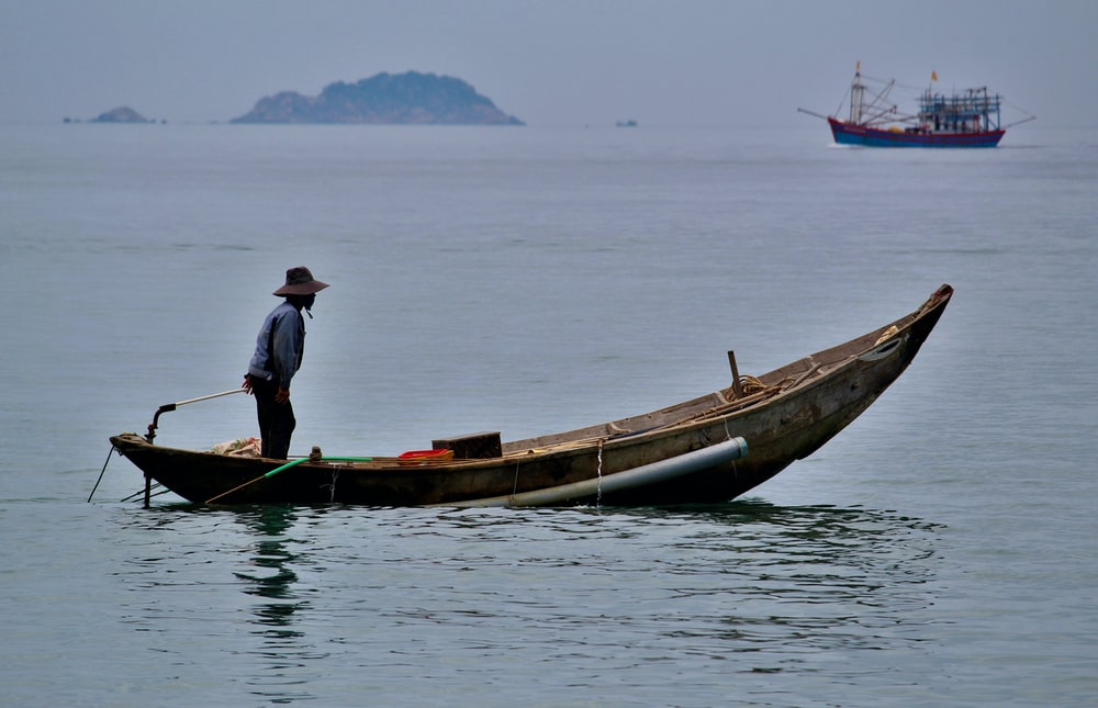 man riding fishing boat on body of water