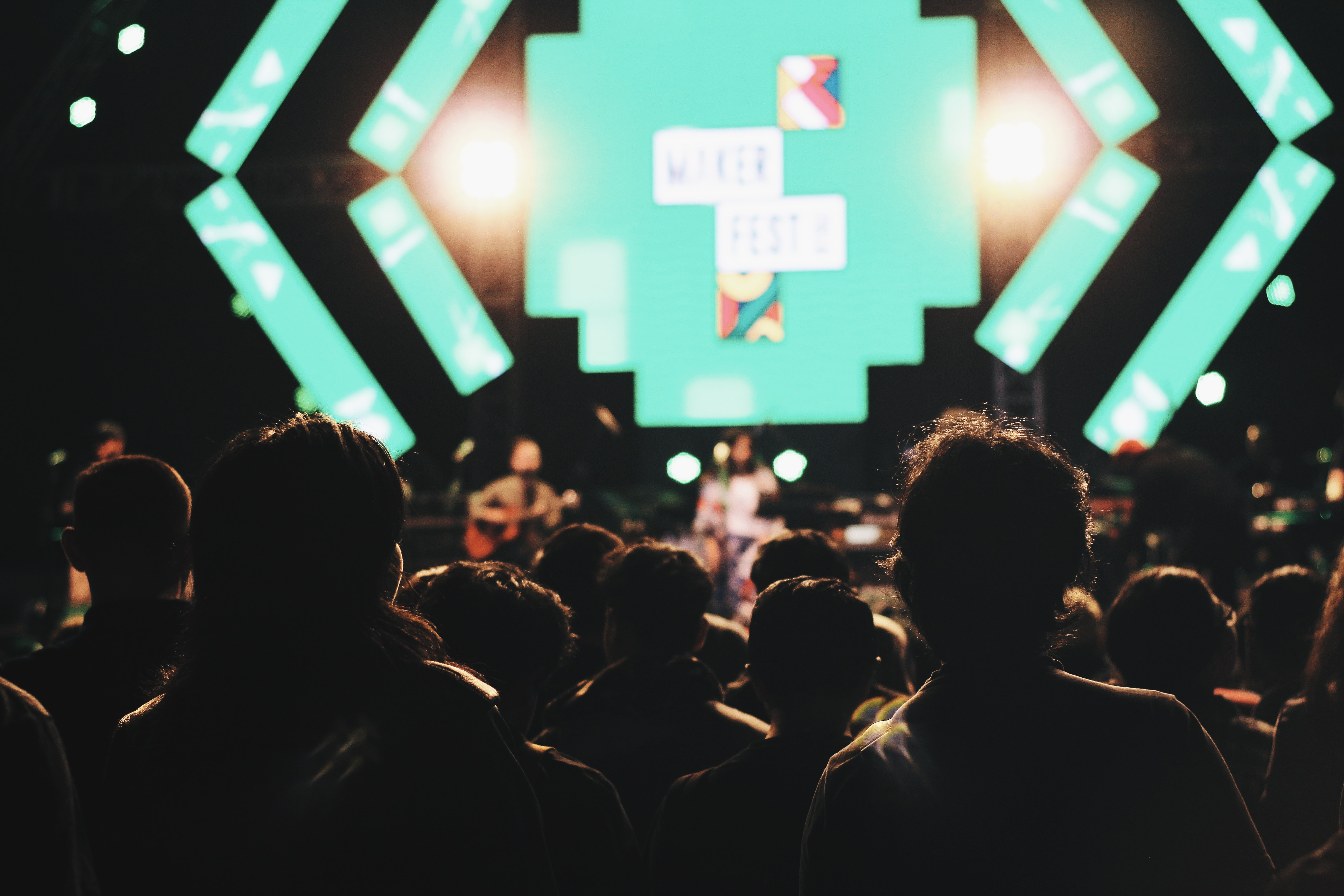 silhouette of crowd of people facing the performer at the stage