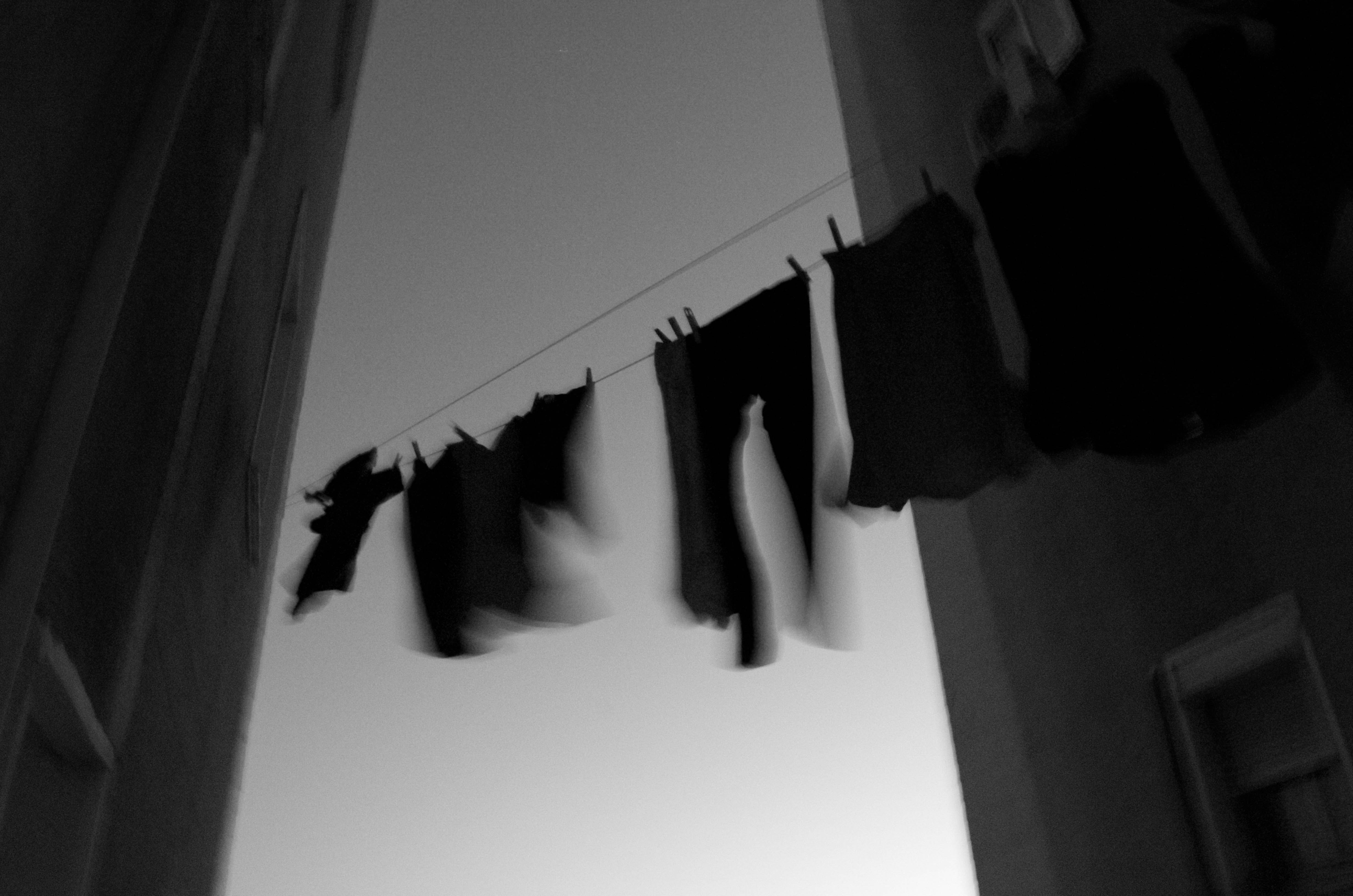 grayscale clothes hanging on cable