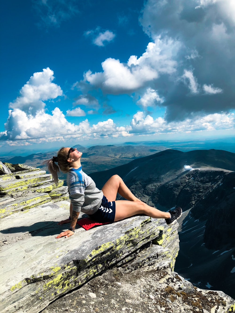 woman sitting on peak of mountain