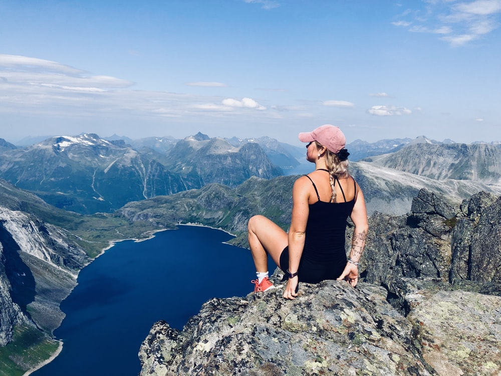 woman sitting on mountain cliff