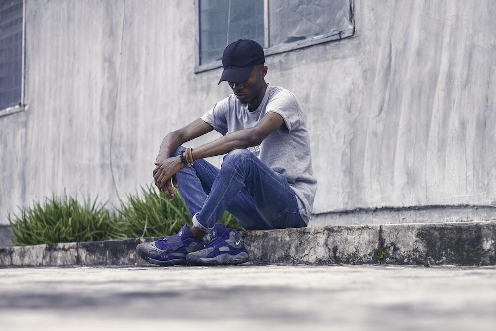 man in gray shirt sitting on concrete sideway
