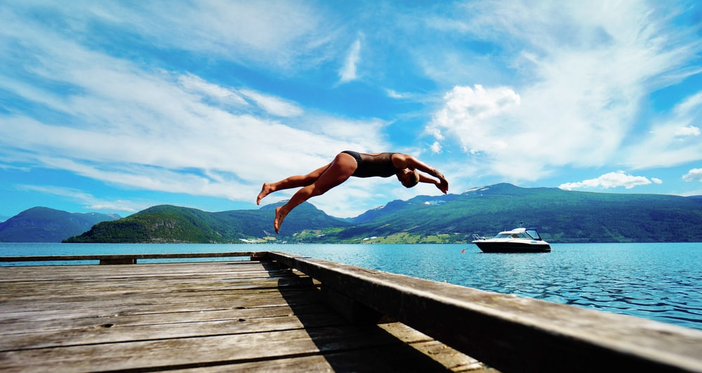 person jumping on body of water at daytime