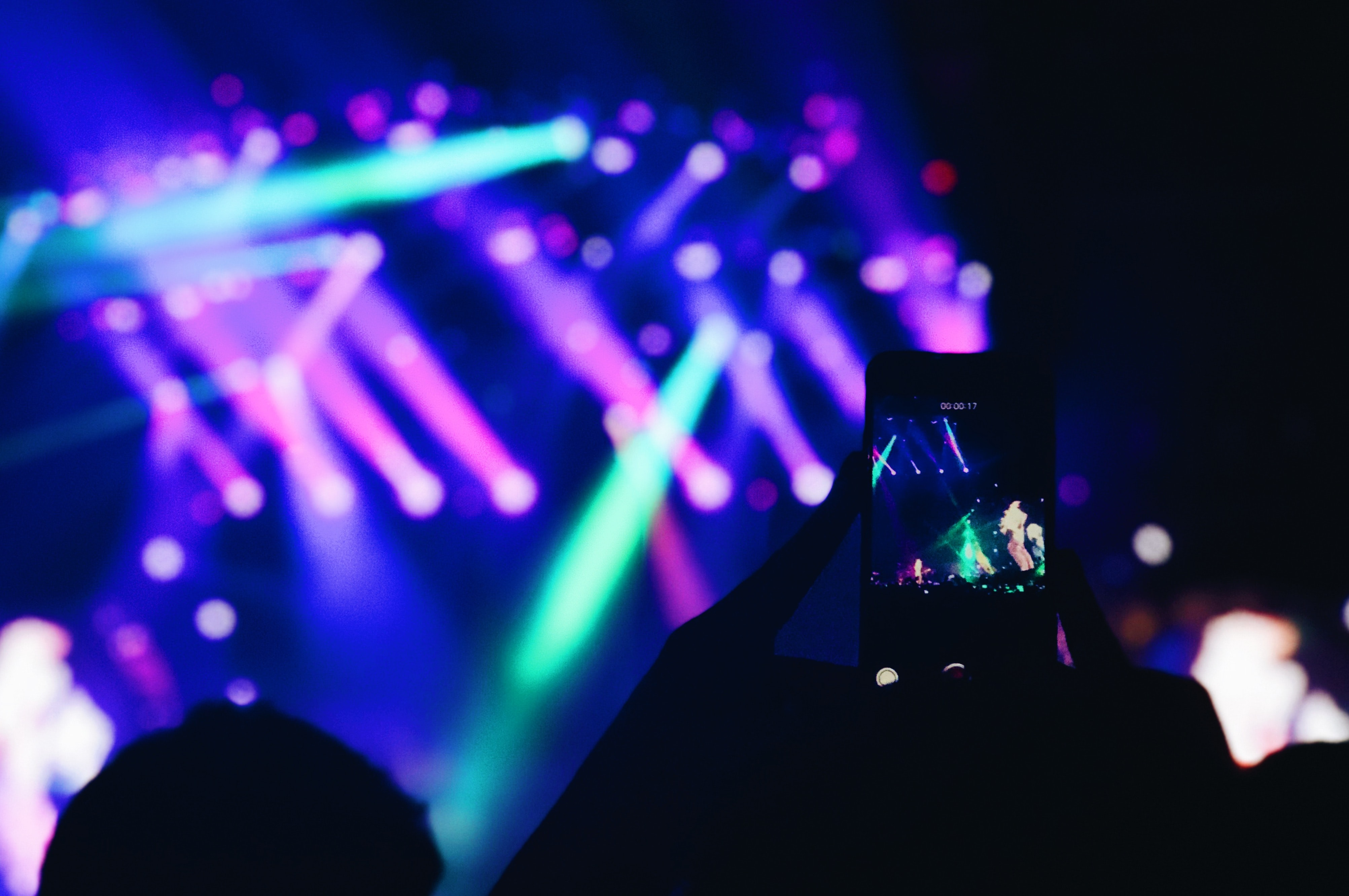 person taking photo of concert