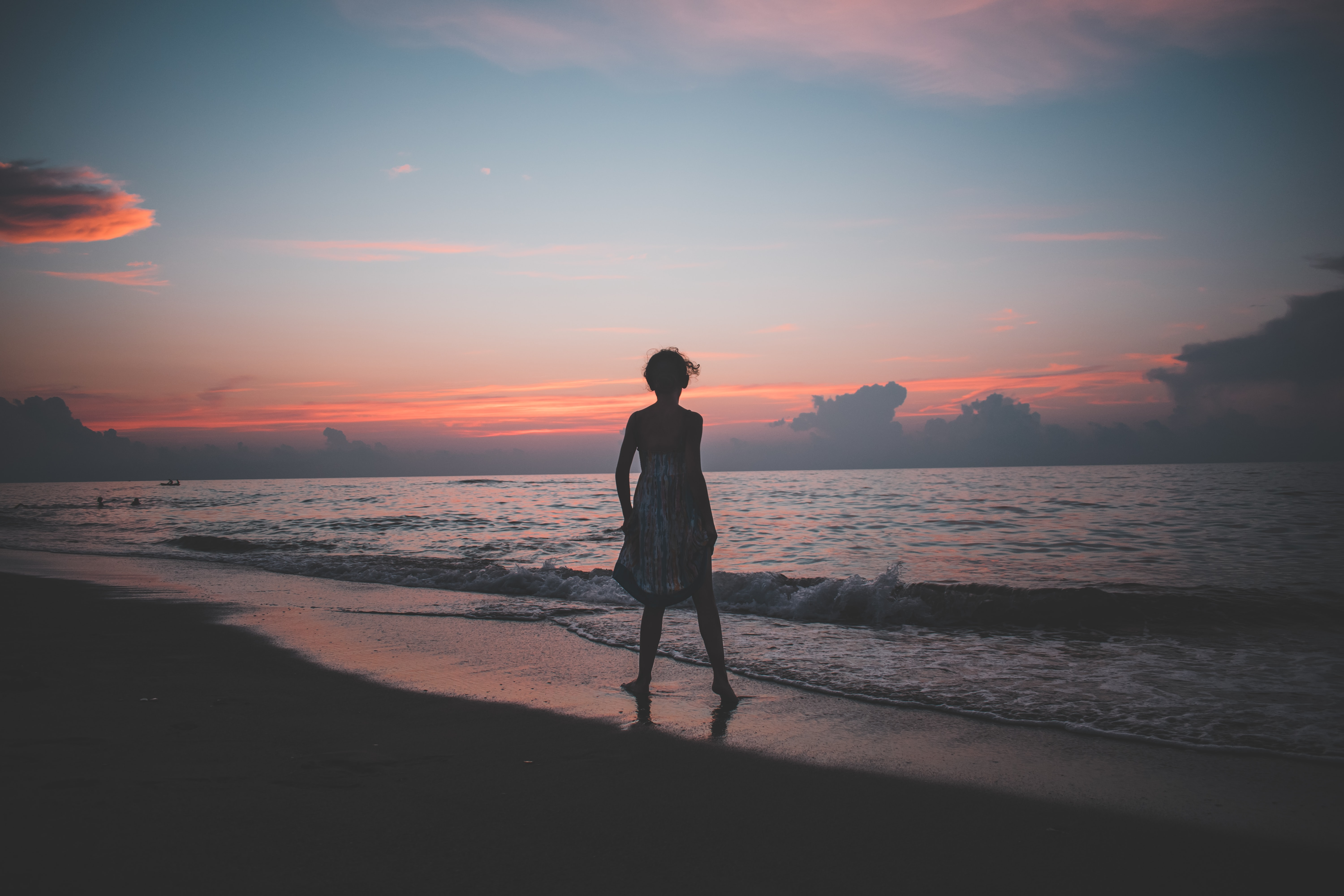 woman standing on the seashore during golden hour