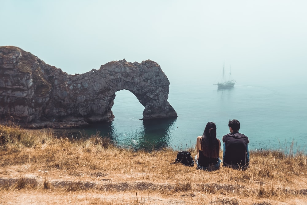 man and woman sitting beside rock formation