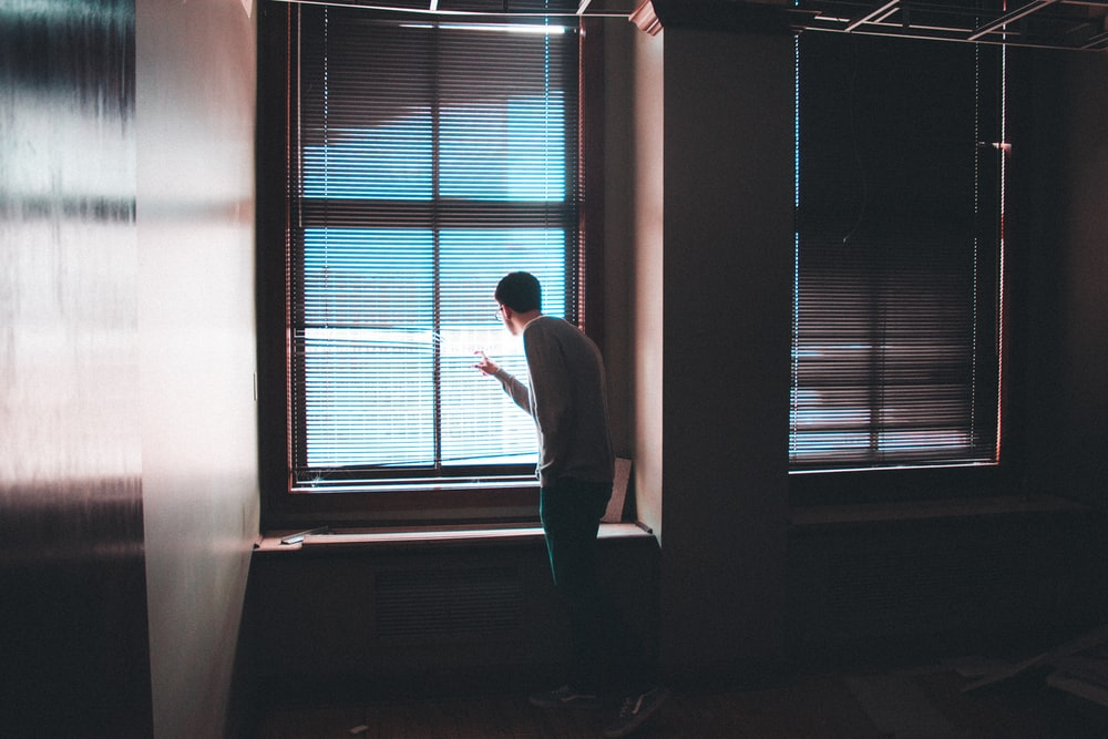 man standing near window inside building