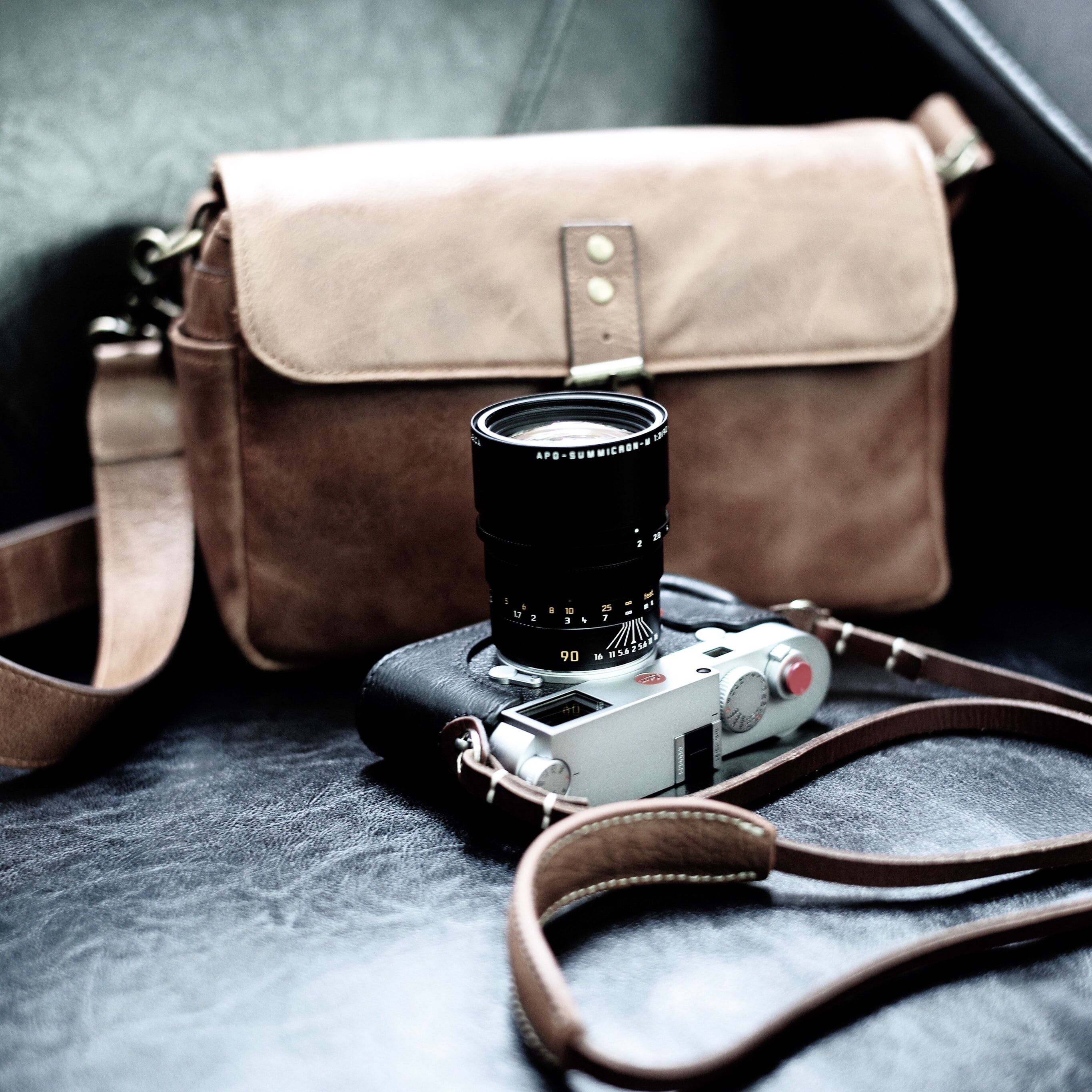 gray and black DSLR camera beside brown leather sling bag