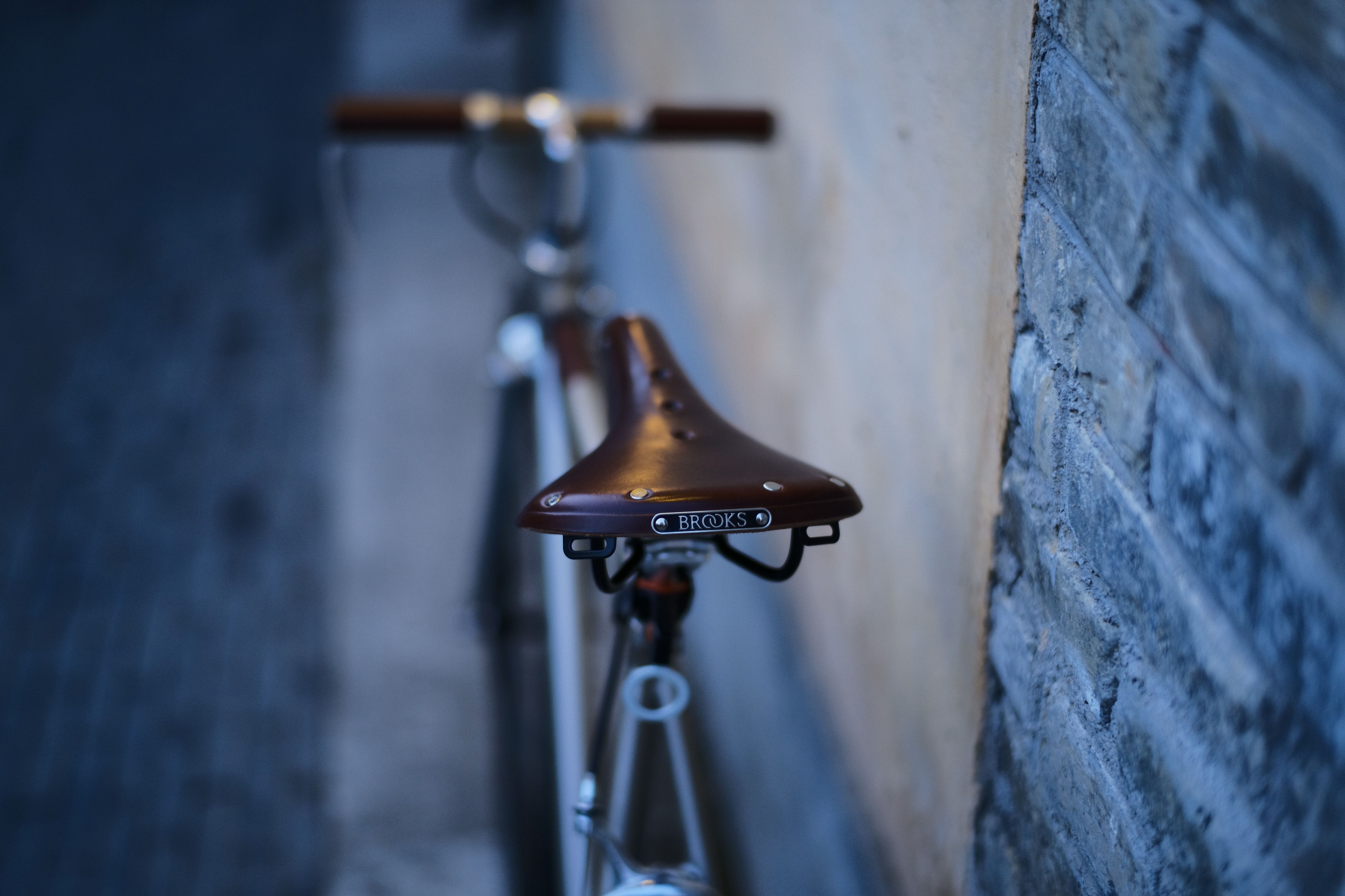 brown bicycle parked beside wall