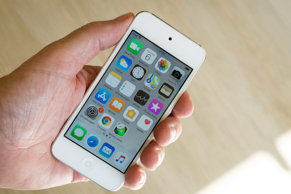 person holding white iPod touch