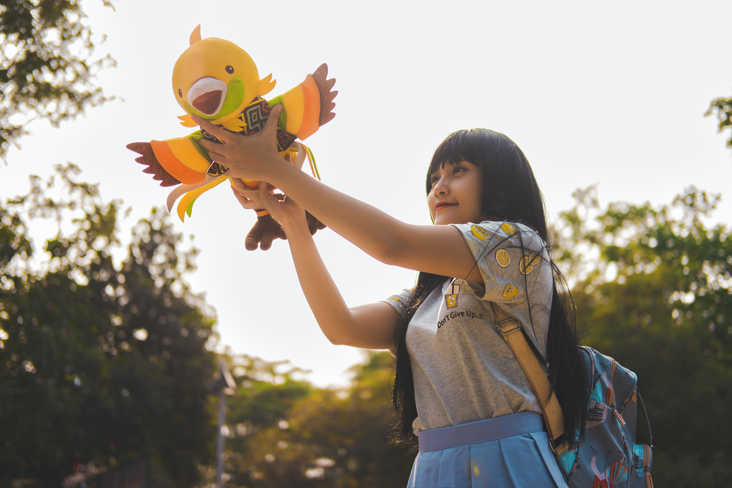 girl playing on bird plush toy