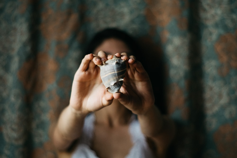 selective focus photography of woman showing conch shell